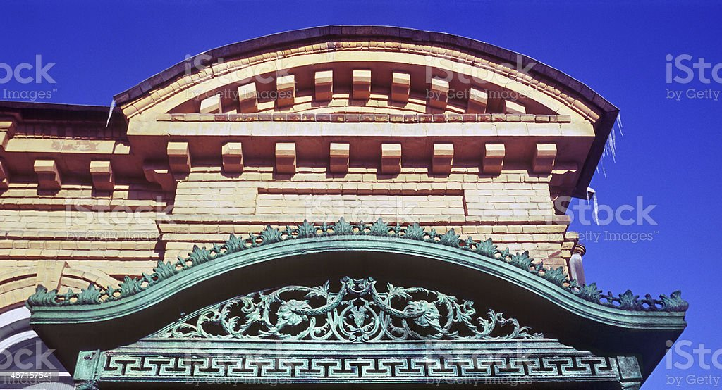 Cast iron Fronton above main entrance to the old building. royalty-free stock photo