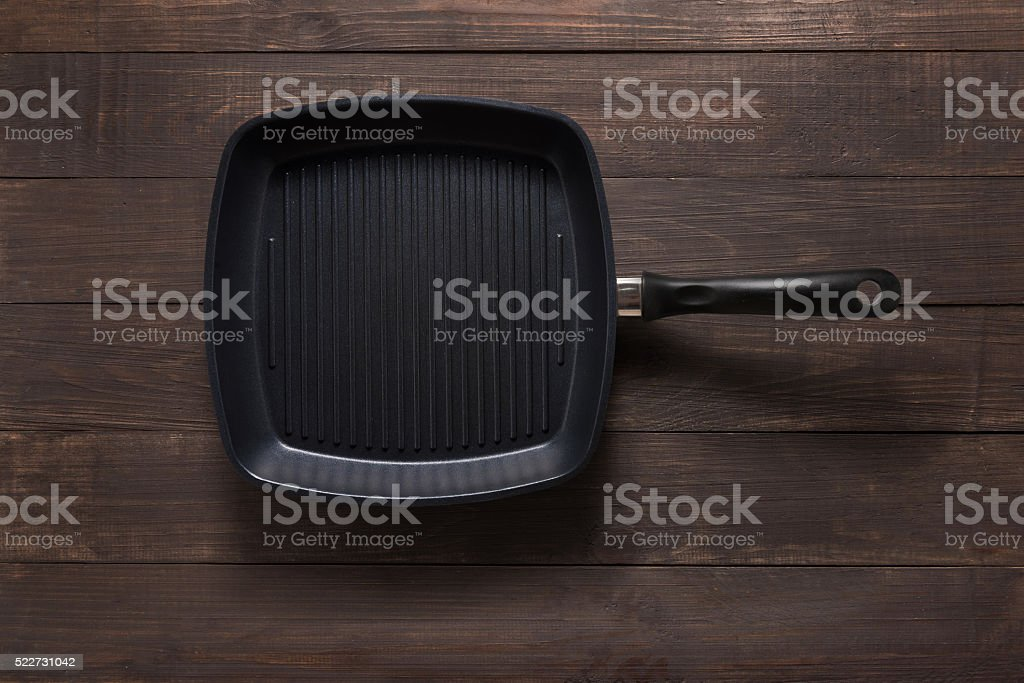 Cast iron griddle pan on wooden background stock photo