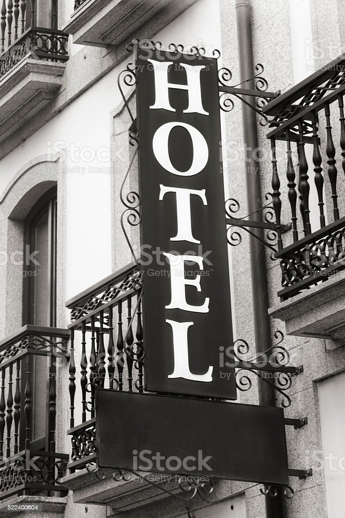 Cast iron hotel sign on building facade with balconies. stock photo
