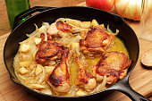 Cast iron pan of cider-braised chicken with vegetables