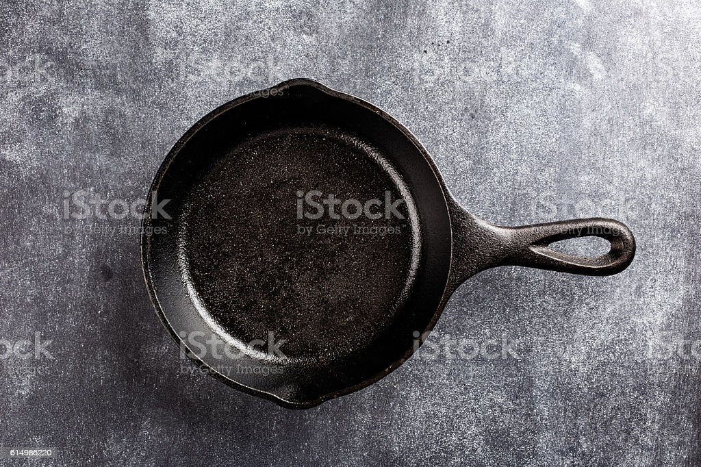 cast iron pan on dark background stock photo
