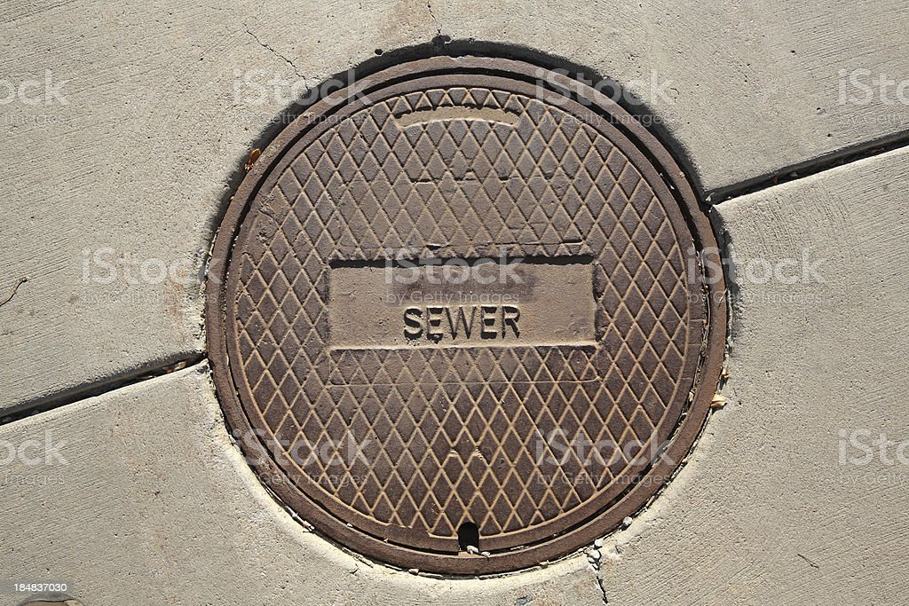 cast iron sewer manhole cover in a sidewalk stock photo