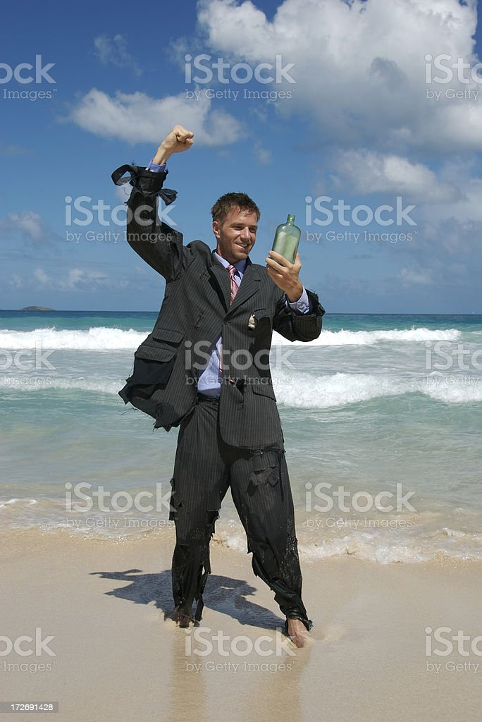 Castaway Businessman Celebrates Message in a Bottle royalty-free stock photo