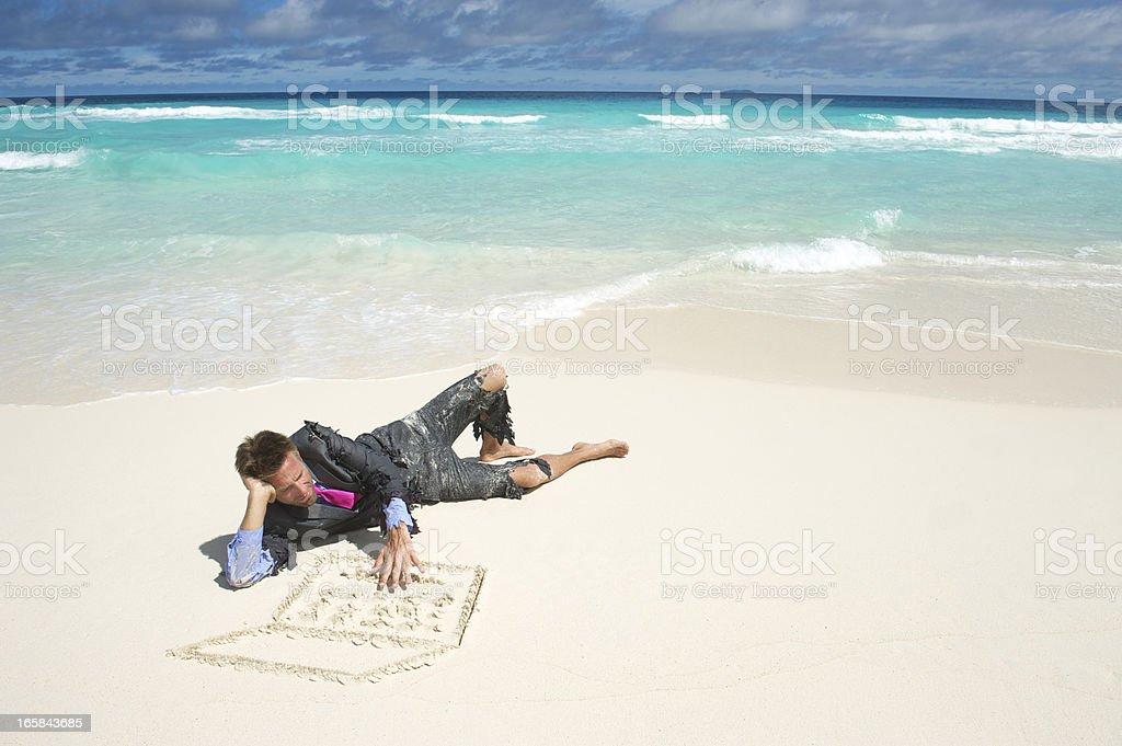 Castaway Businessman Lies on Beach Using Sand Laptop royalty-free stock photo