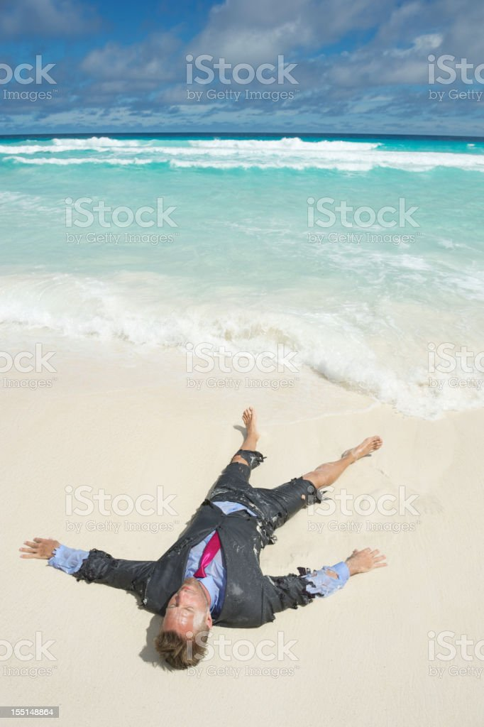 Castaway Businessman Lies Stranded on Tropical Beach stock photo