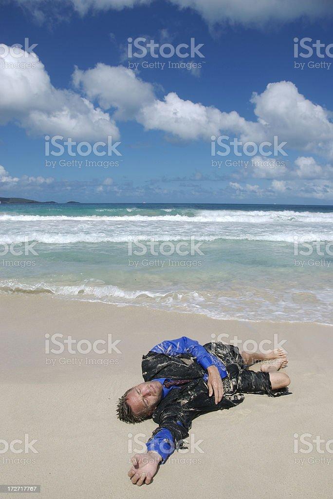Castaway Businessman Lies Washed Ashore royalty-free stock photo