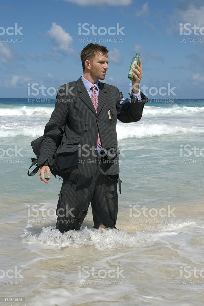 Castaway Businessman Looks at Message in a Bottle royalty-free stock photo