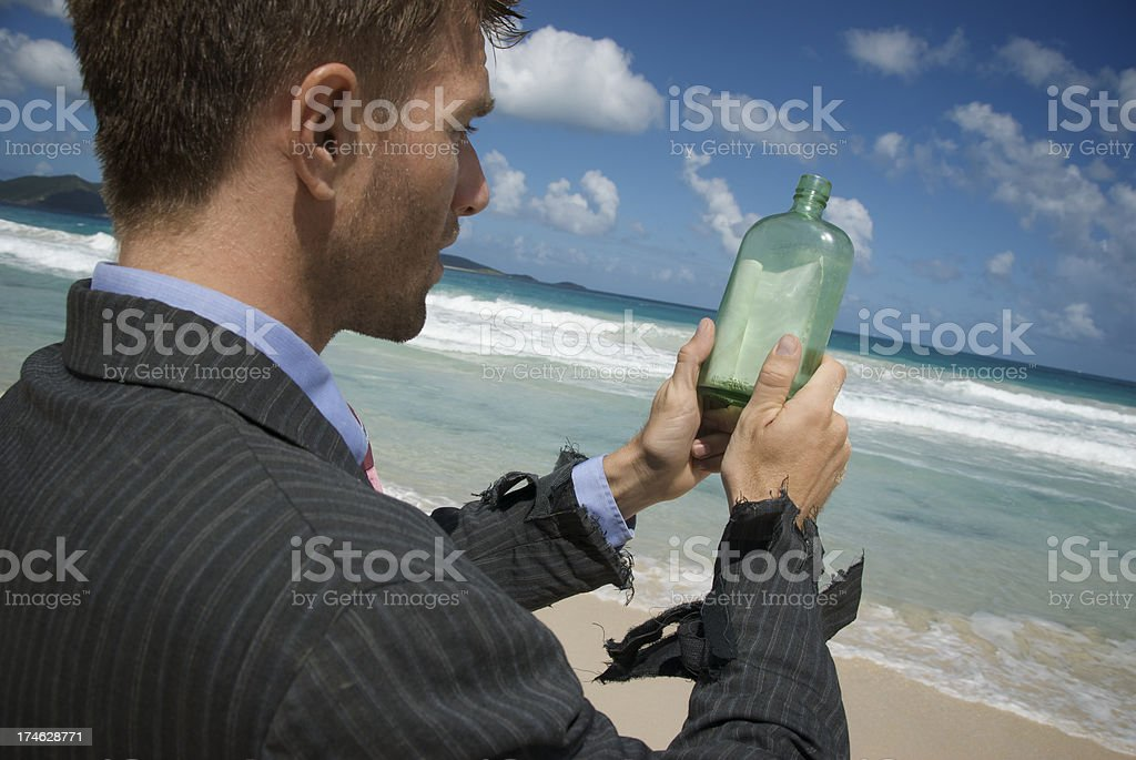 Castaway Businessman Message in a Bottle royalty-free stock photo