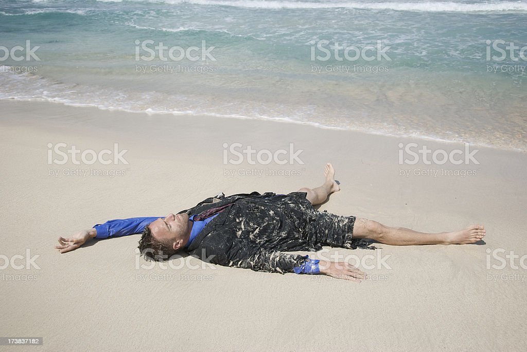Castaway Businessman Passed Out on Beach royalty-free stock photo
