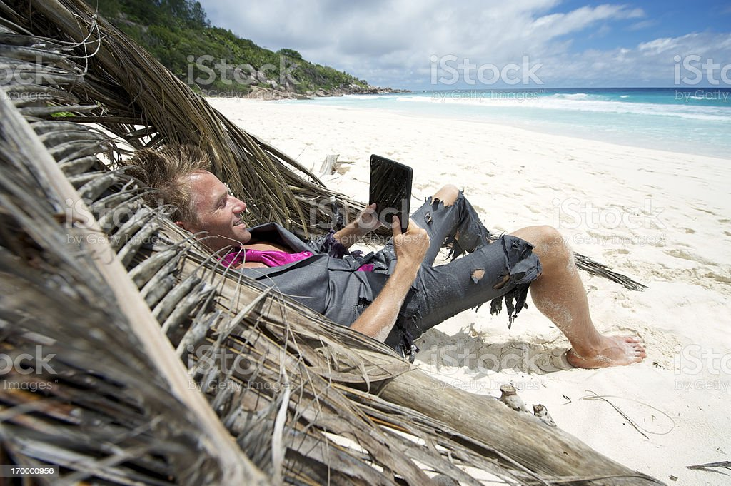 Castaway Businessman Relaxes on Beach with Tablet Computer stock photo
