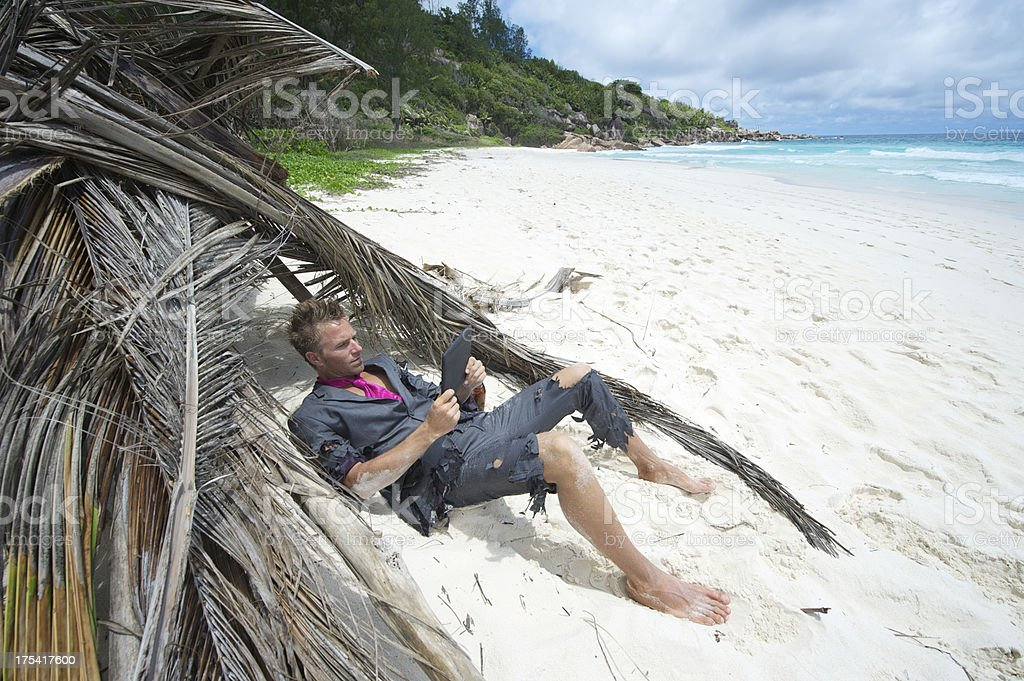 Castaway Businessman Relaxes with Digital Tablet on Beach royalty-free stock photo