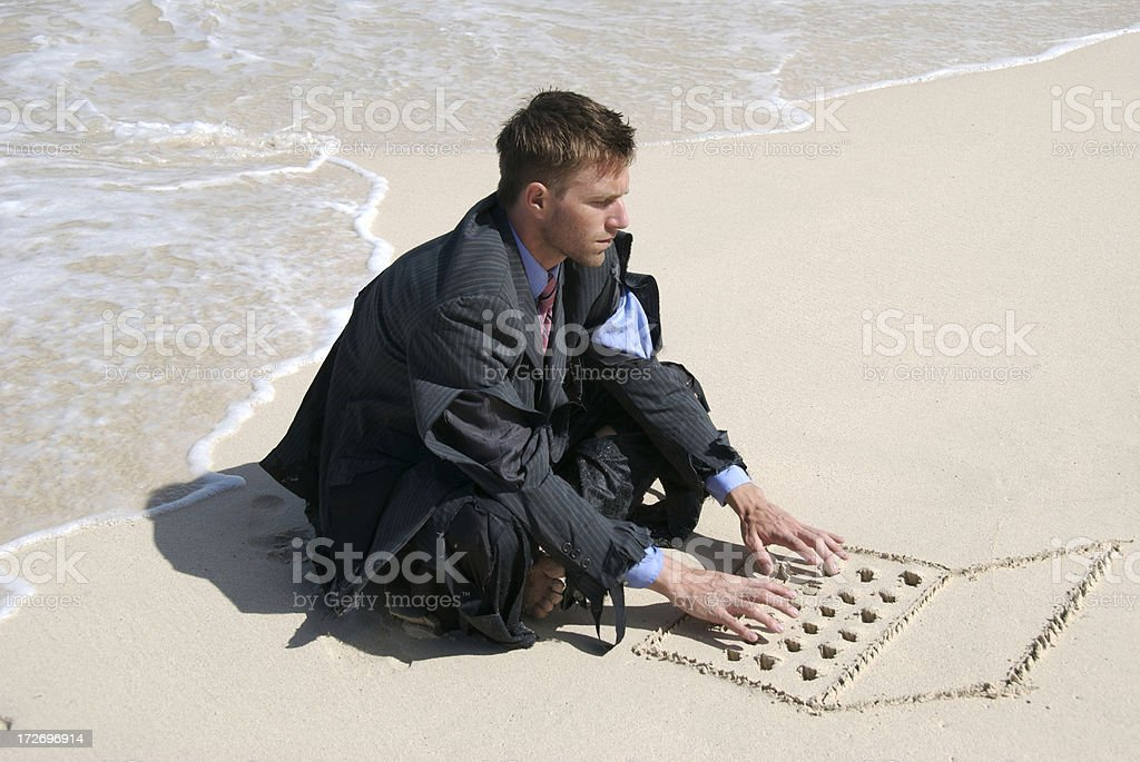Castaway Businessman Sits Typing on Sand Laptop royalty-free stock photo