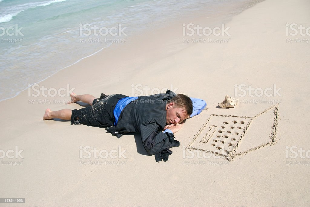 Castaway Businessman Sleeping by his Laptop Computer on the Beach stock photo