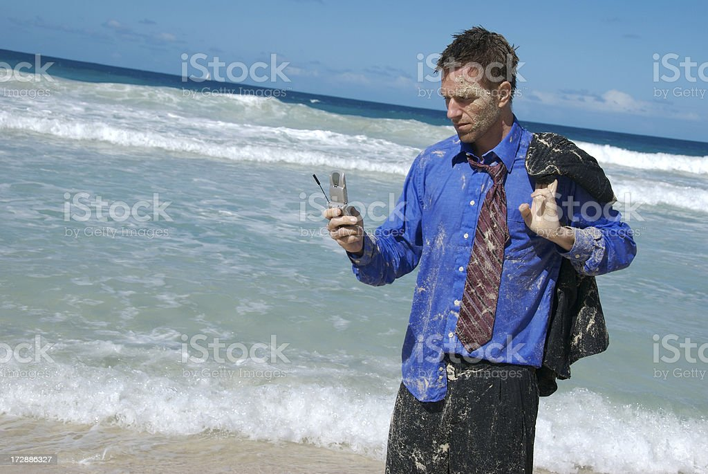 Castaway Businessman Standing in Surf Texting on Mobile Phone royalty-free stock photo