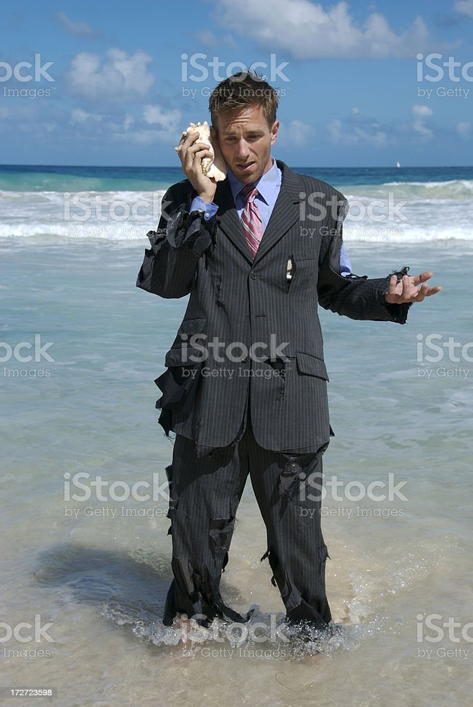 Castaway Businessman Stands in the Waves on Mobile Phone royalty-free stock photo