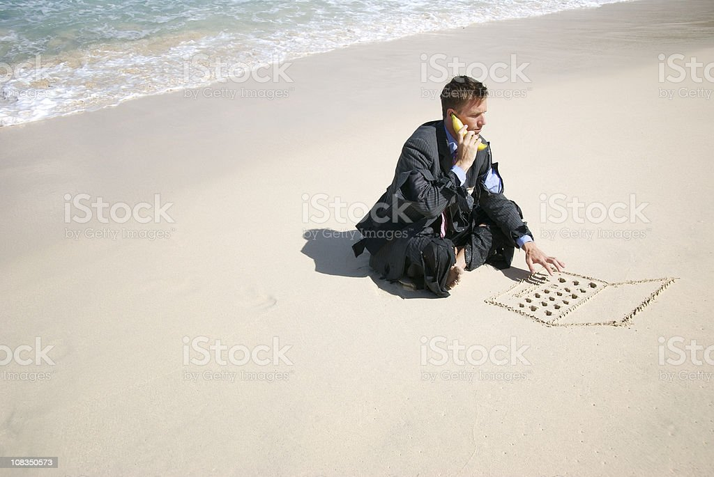 Castaway Businessman Talks w Bananaphone and Types on Sand royalty-free stock photo