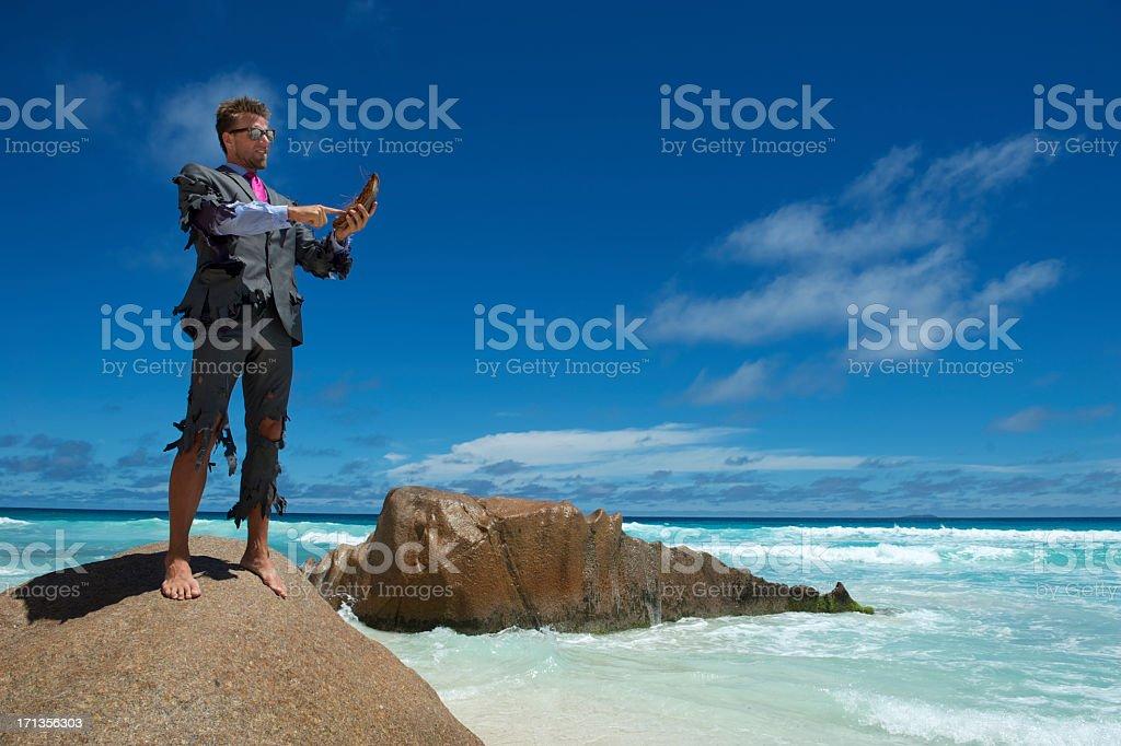 Castaway Businessman Uses Coconut Smartphone on Beach stock photo