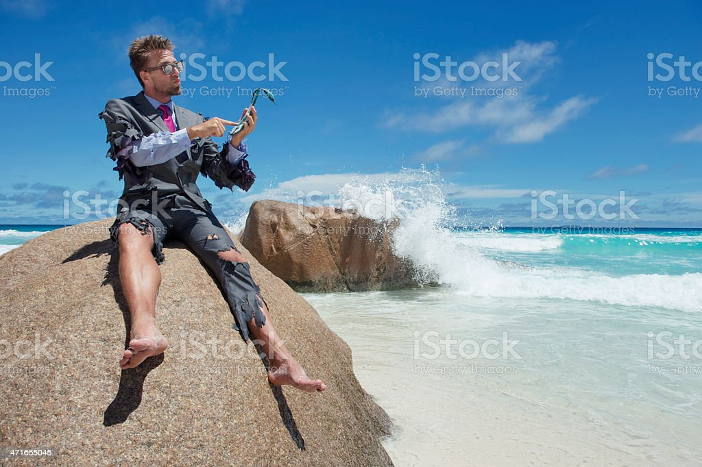Castaway Businessman Uses Flip-Flip Smartphone on Beach stock photo