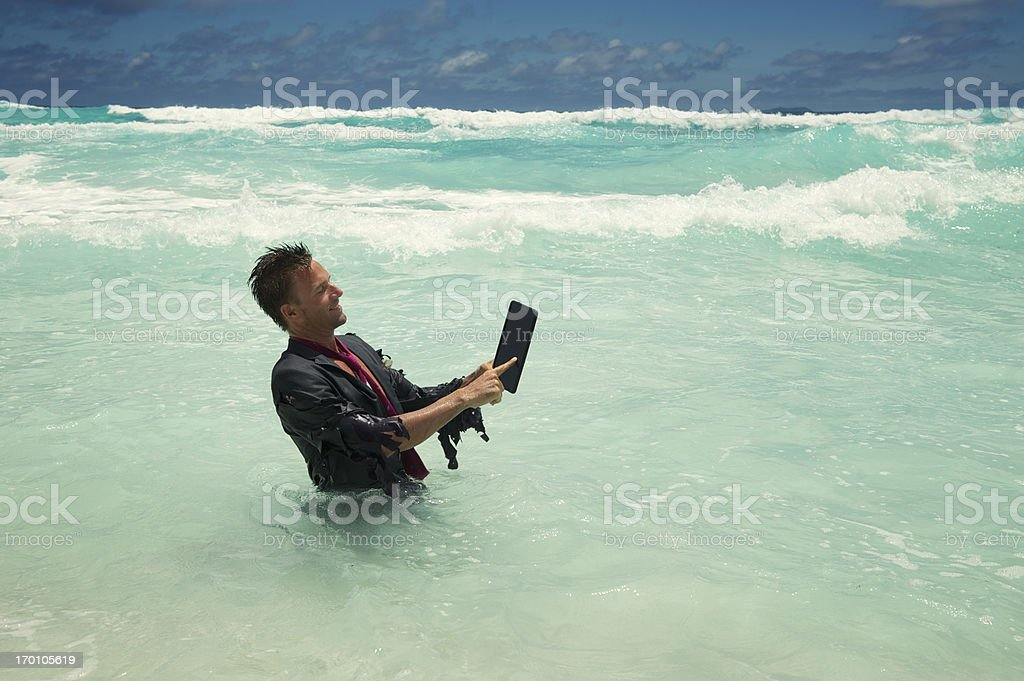 Castaway Businessman Uses Tablet Computer in Sea royalty-free stock photo