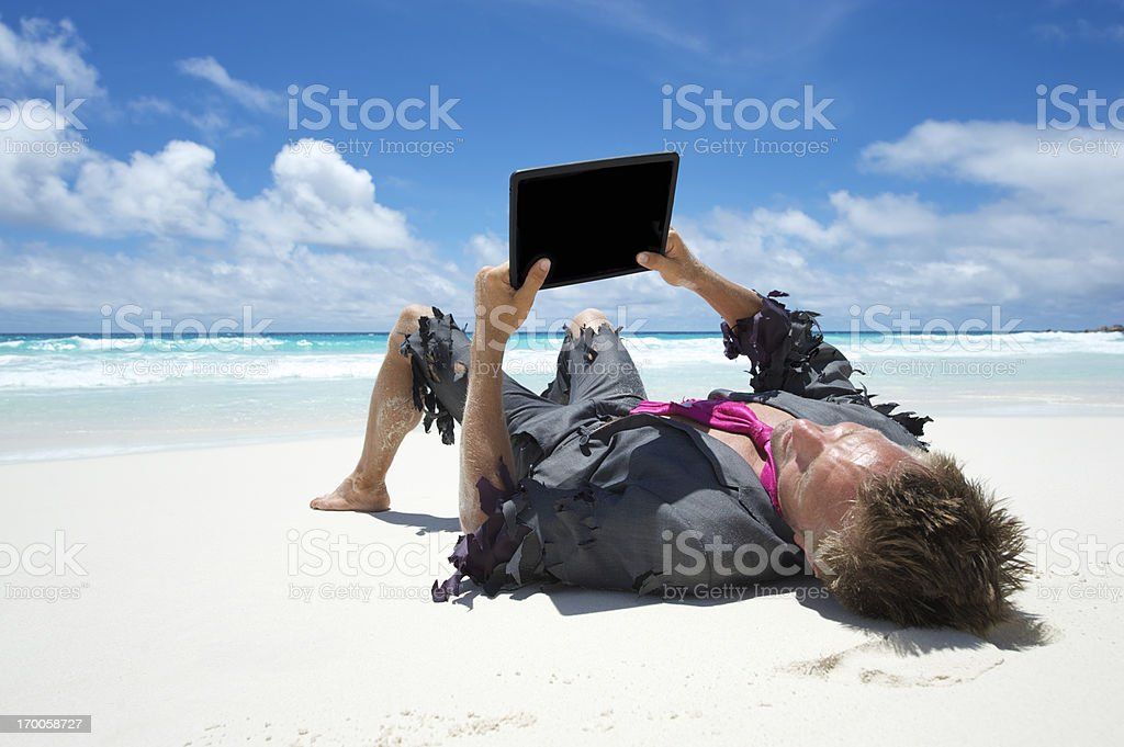 Castaway Businessman Uses Tablet Computer on Beach royalty-free stock photo