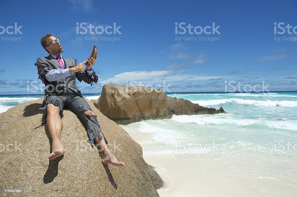 Castaway Businessman Using Coconut Husk Smartphone on Beach royalty-free stock photo