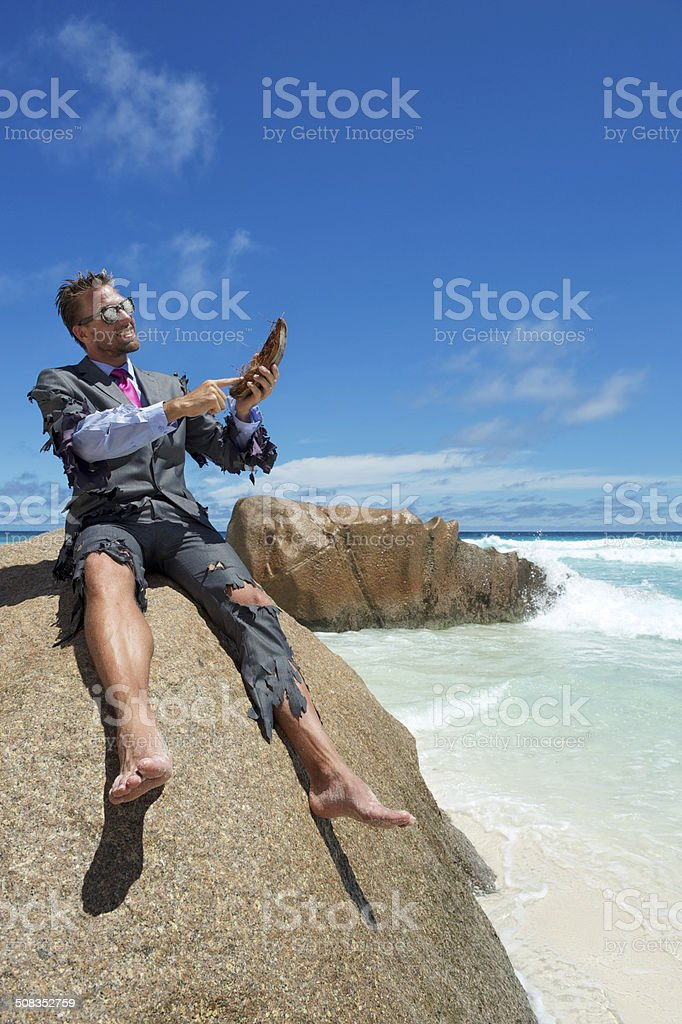 Castaway Businessman Using Coconut Husk Tablet on Beach stock photo