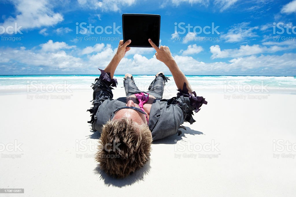 Castaway Businessman Using Tablet Computer Outdoors on White Beach royalty-free stock photo