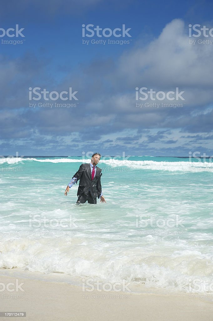 Castaway Businessman Washes Ashore in Tropical Waves royalty-free stock photo