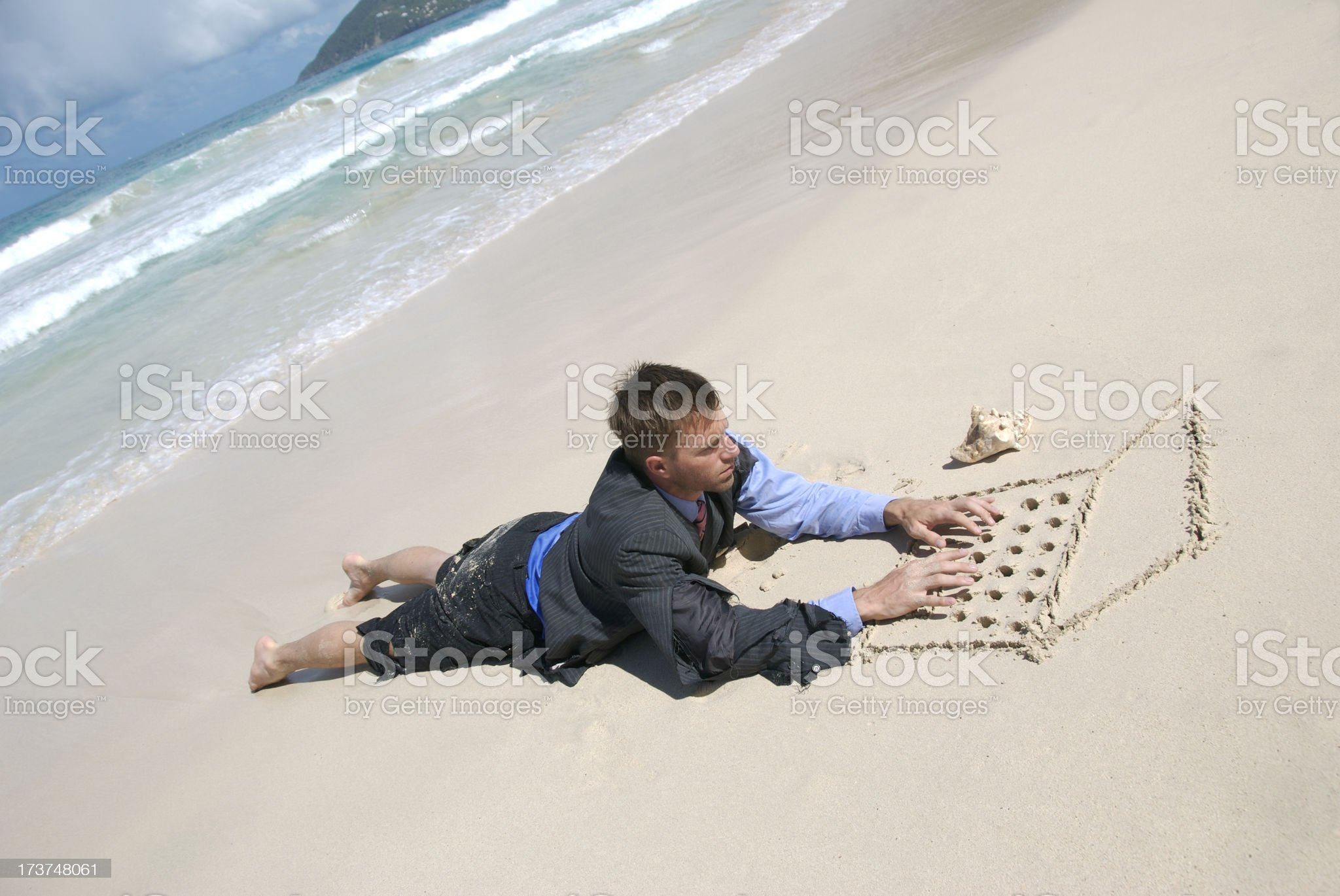 Castaway Businessman Working Outdoors Typing on Sand Computer royalty-free stock photo