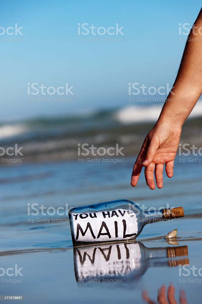 Castaway hand reaches for You Have Mail message in bottle royalty-free stock photo