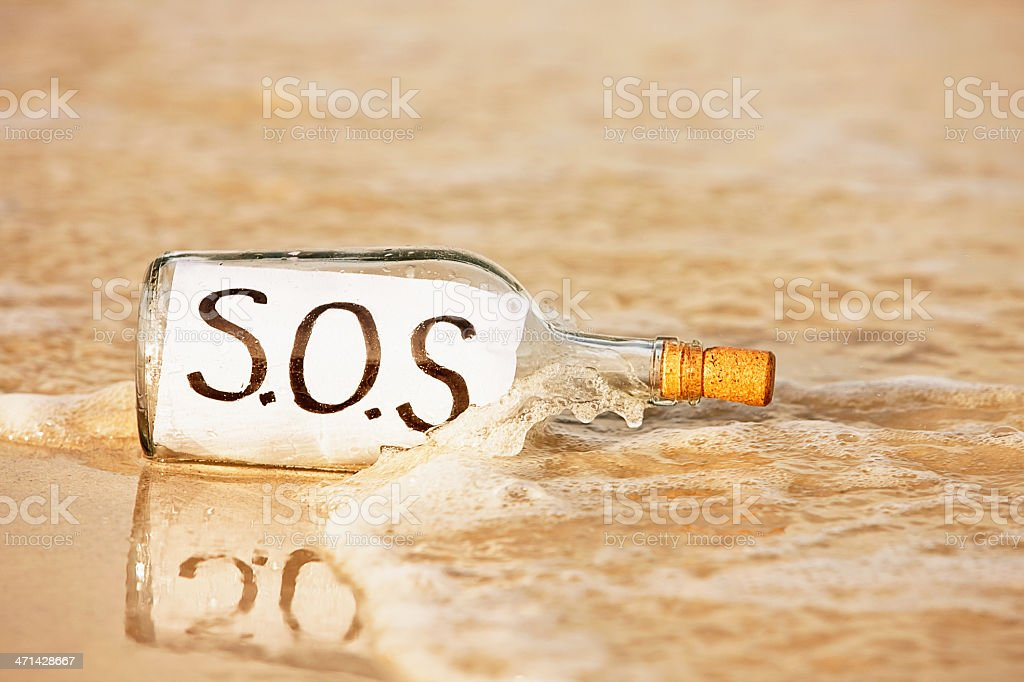 Castaway needs help urgently so sends SOS message in bottle royalty-free stock photo