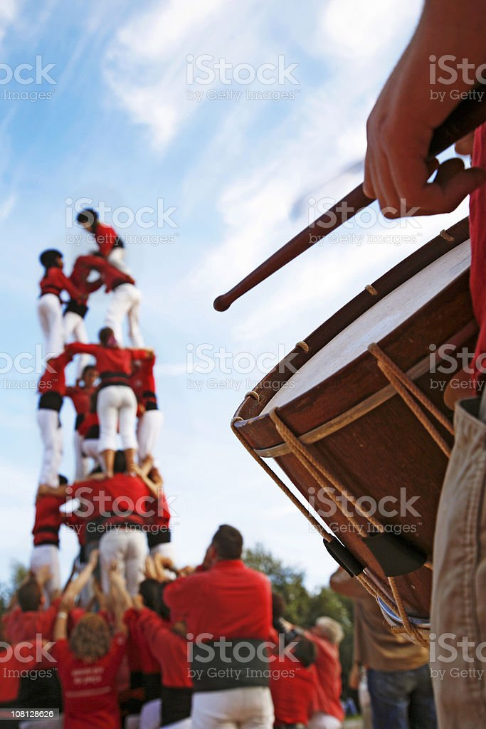 Castellers and Man Playing Drum on Sunny Day stock photo