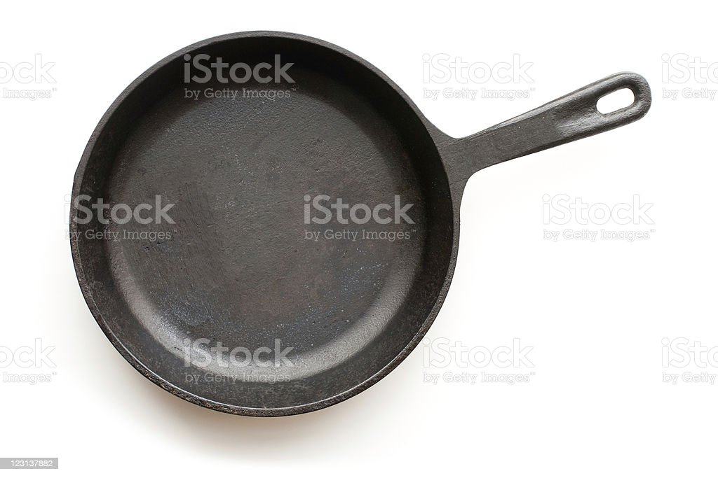 A cast-iron frying pan set against a white background stock photo