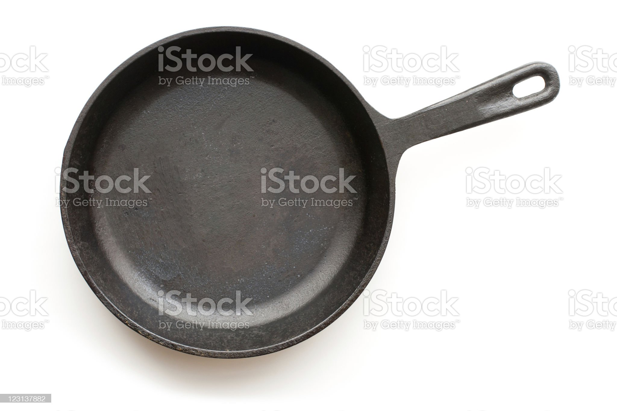 A cast-iron frying pan set against a white background royalty-free stock photo