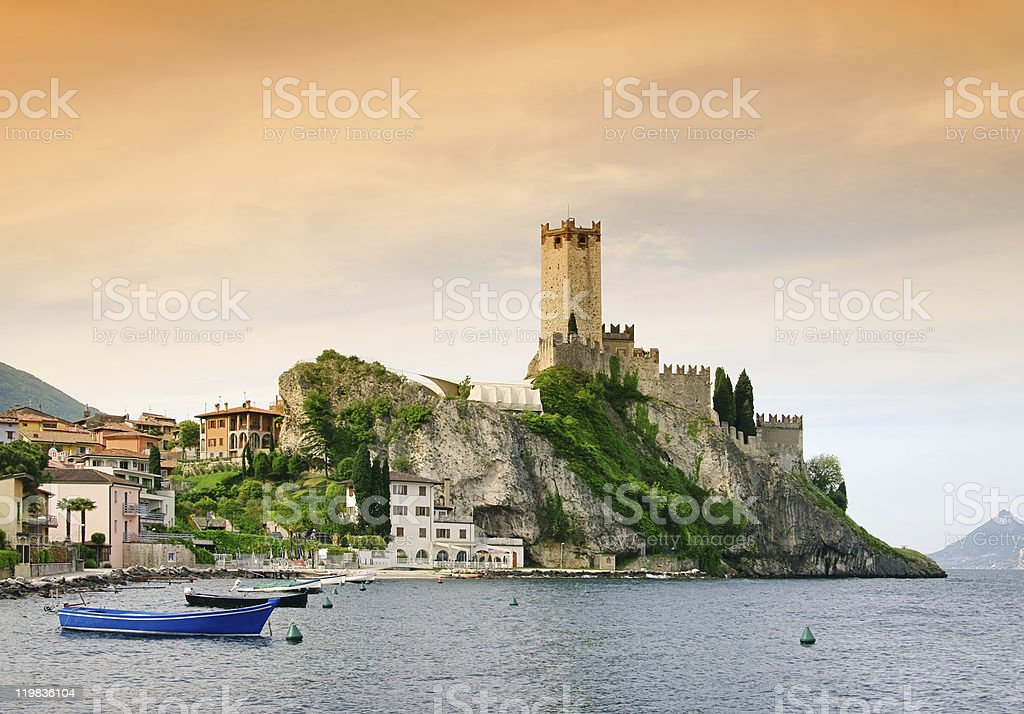 Castle at sunset on an island cliff with small boats near stock photo