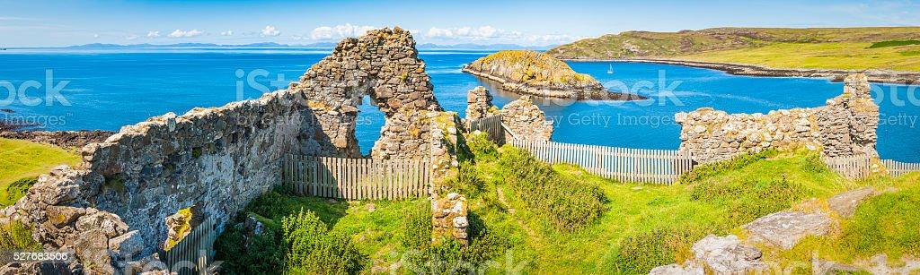 Castle ruins overlooking blue ocean green islands panorama Skye Scotland stock photo