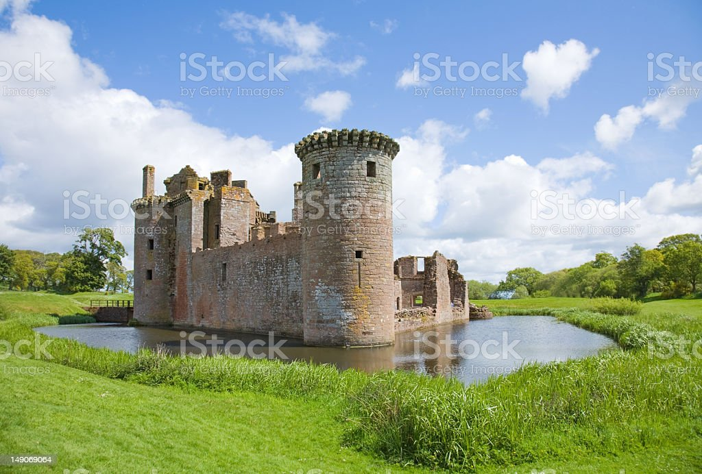 Castle surrounded by moat and green grass field stock photo