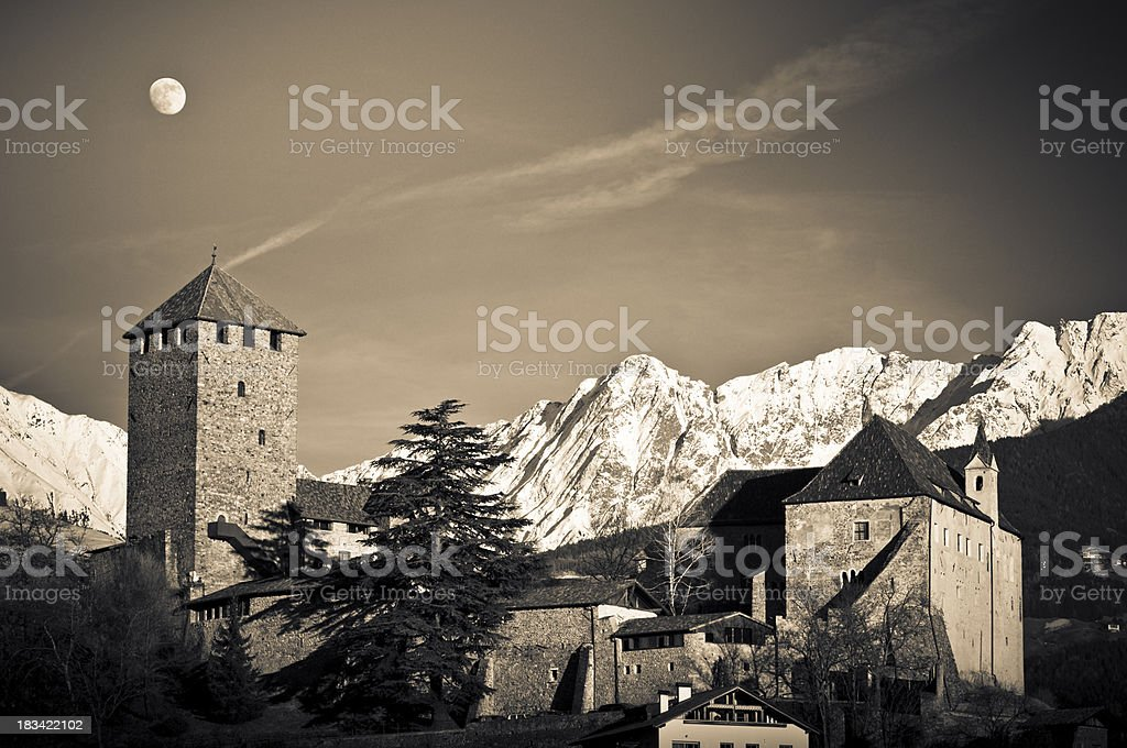 Castle Tyrol with moon and snowy mountains royalty-free stock photo