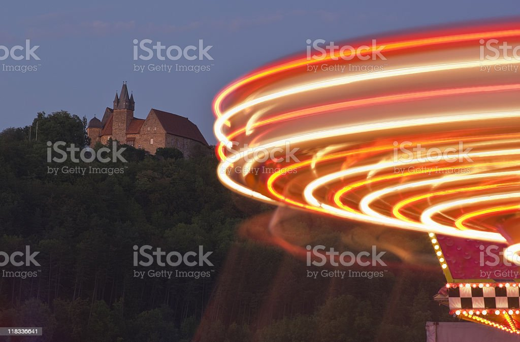 Castle with an illuminated merry-go-round in the twilight stock photo