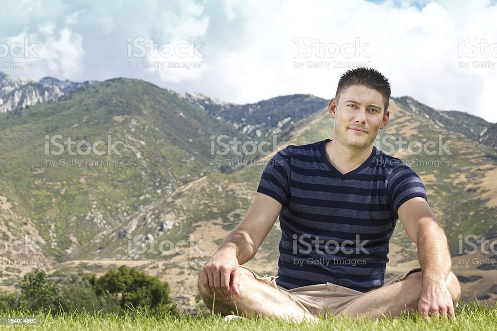Casual and Confident Young Man Sitting Against Mountain Backdrop stock photo