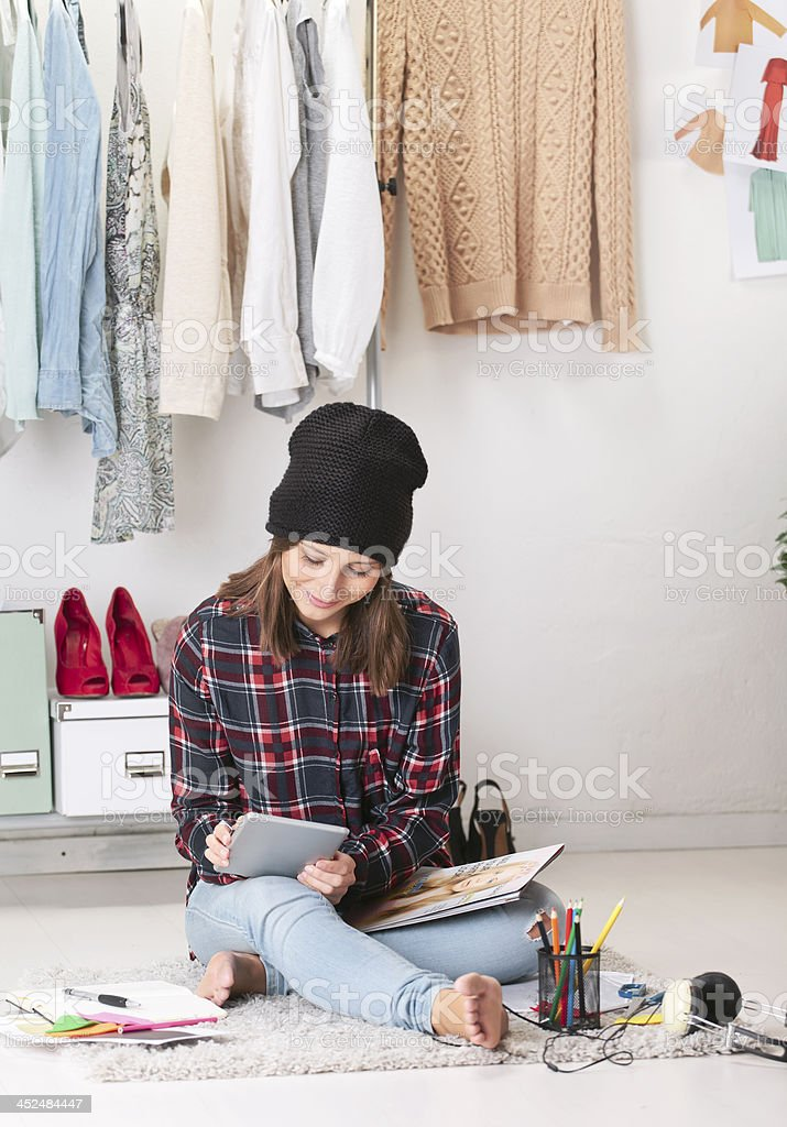 Casual blogger woman working with digital tablet in fashion office. stock photo