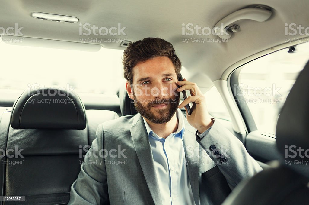 Casual business man on mobile phone in rear of car stock photo