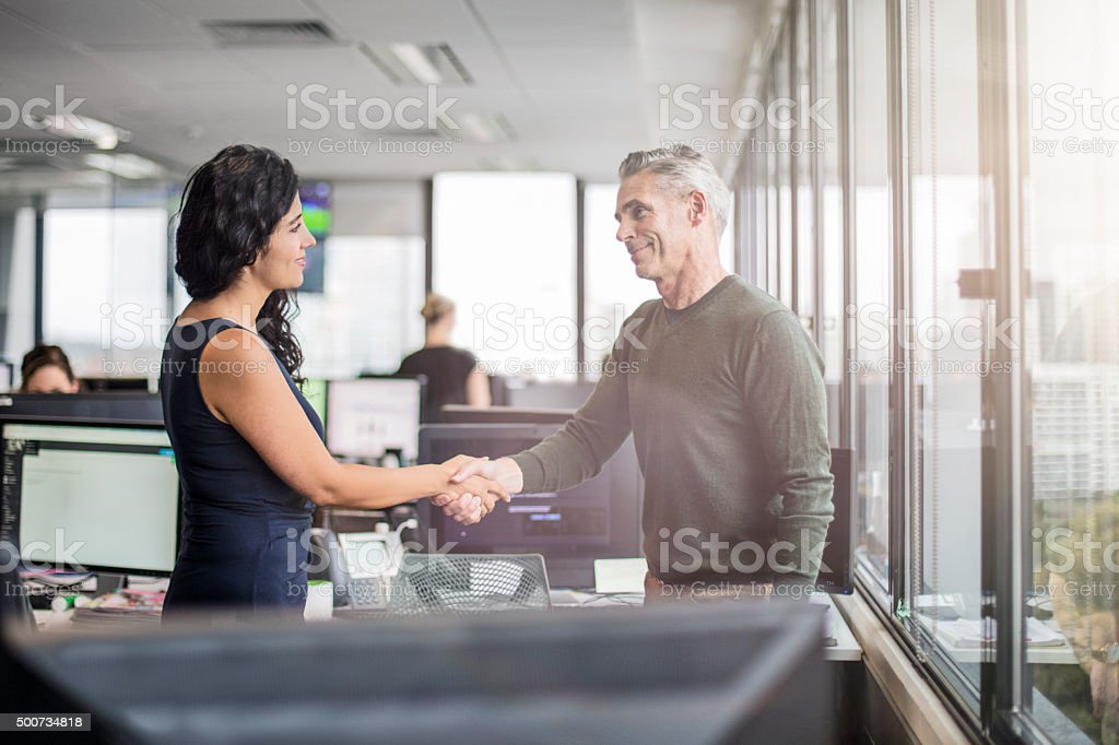 Casual business people shaking hands in the office stock photo