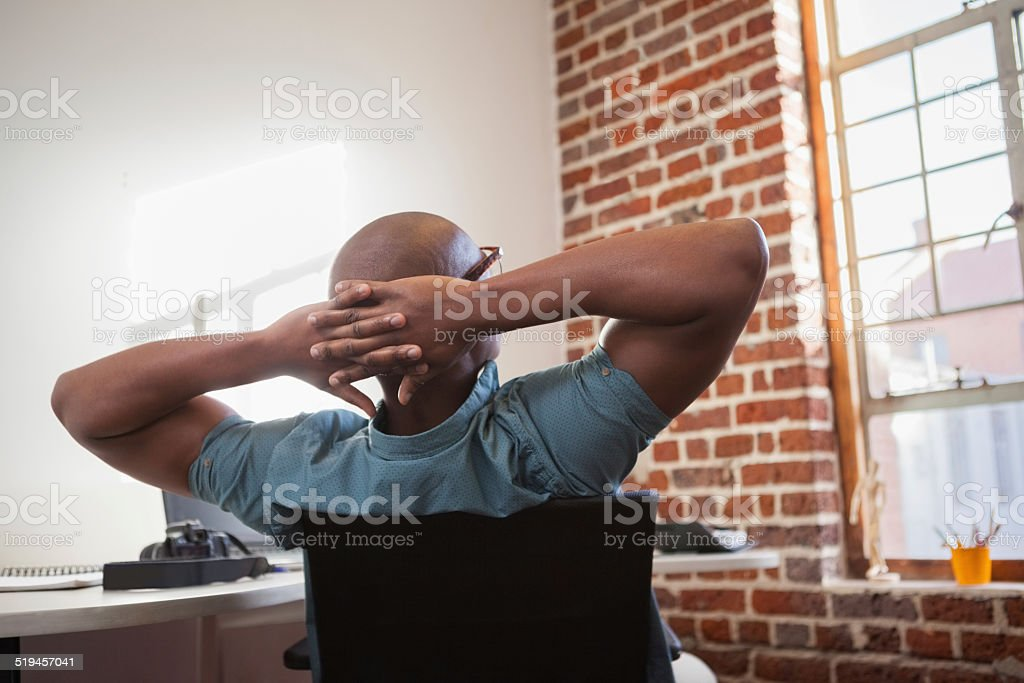 Casual businessman leaning back in chair stock photo