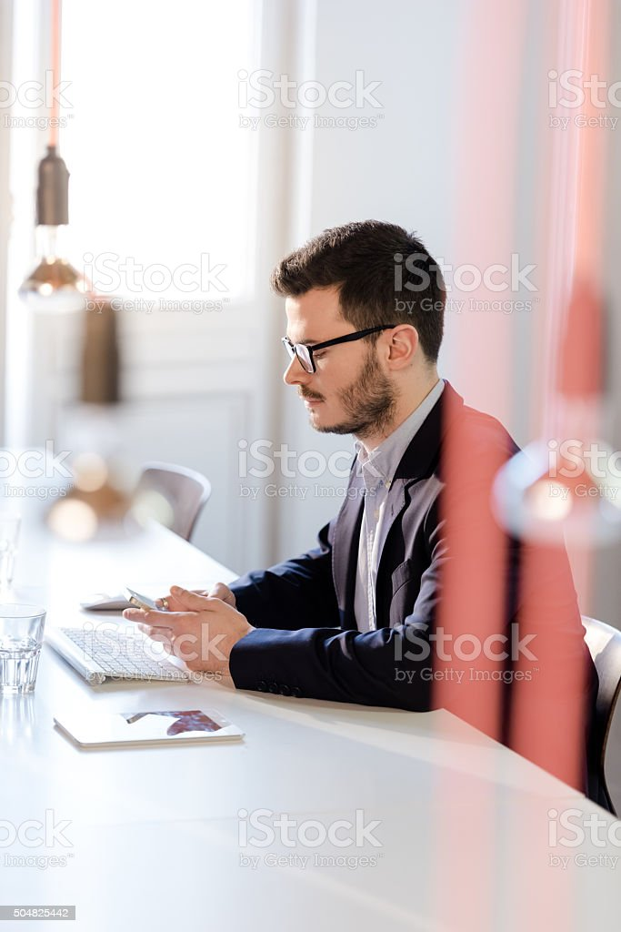 Casual businessman sitting on desk and surfing with smart phone stock photo