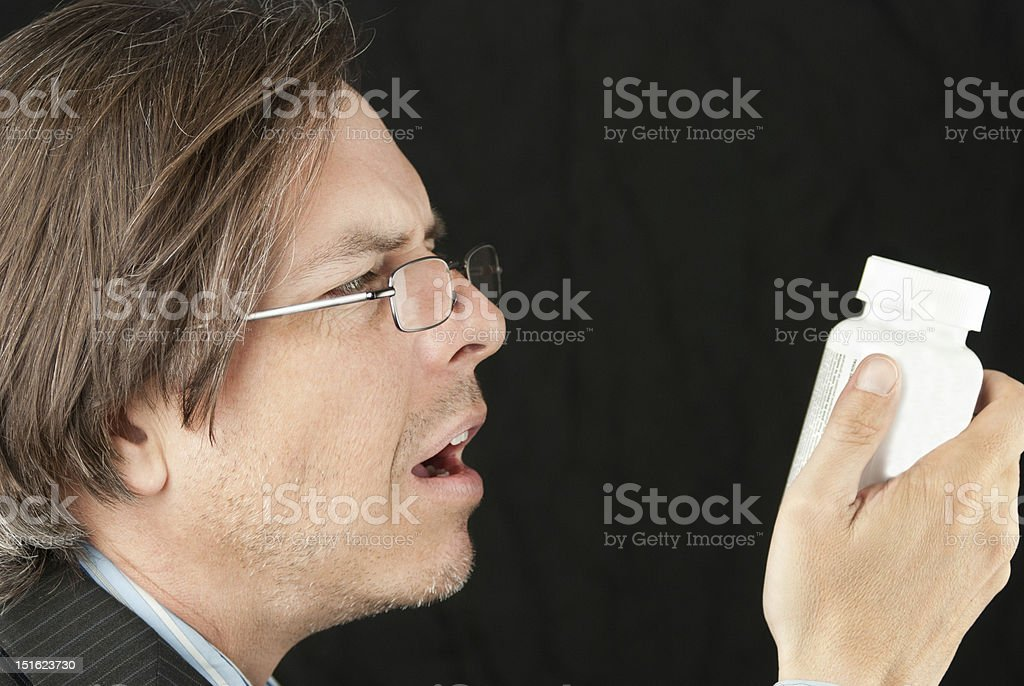 Casual Businessman Wearing Reading Glasses Trying To Read Pill B royalty-free stock photo