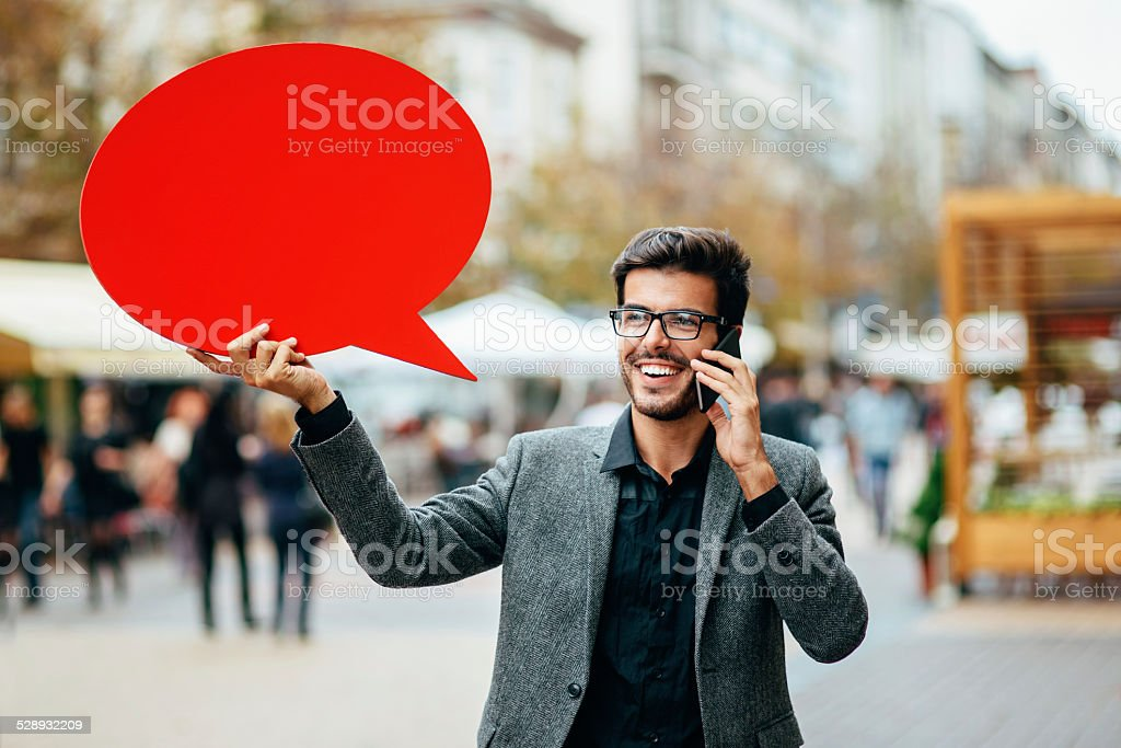Casual businessman with phone and red speech bubble outdoors stock photo
