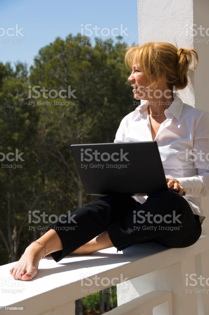 Casual businesswman working with laptop in the terrace royalty-free stock photo