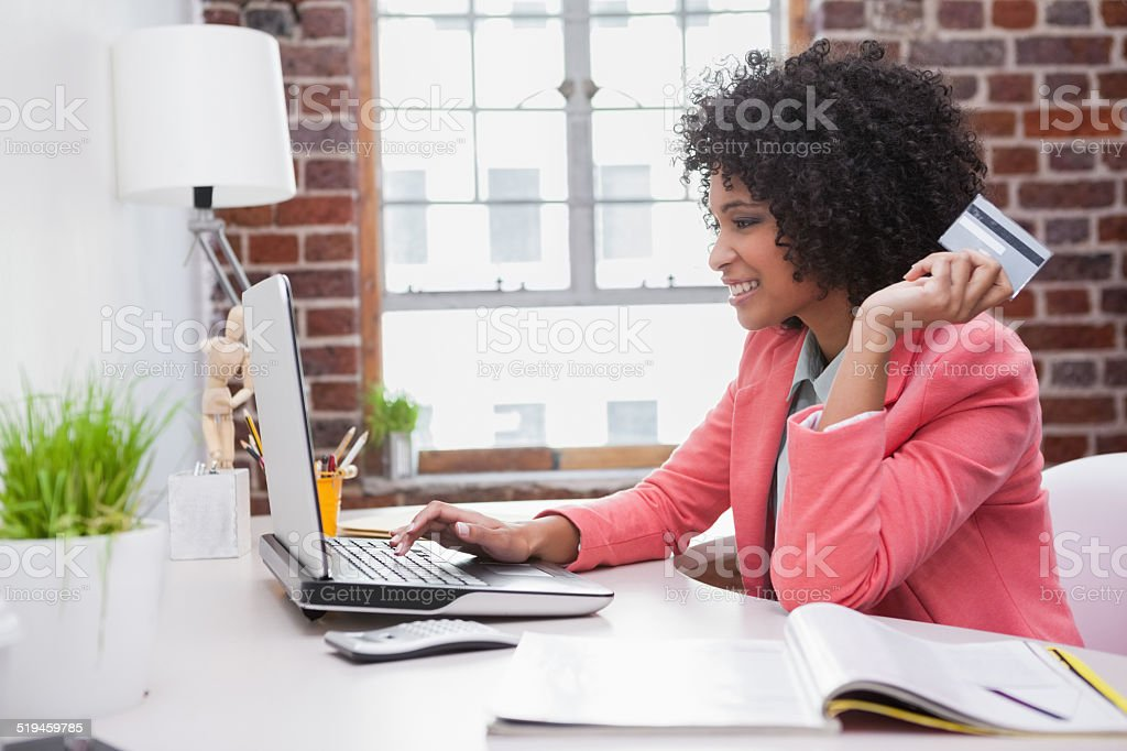 Casual businesswoman shopping online at desk stock photo