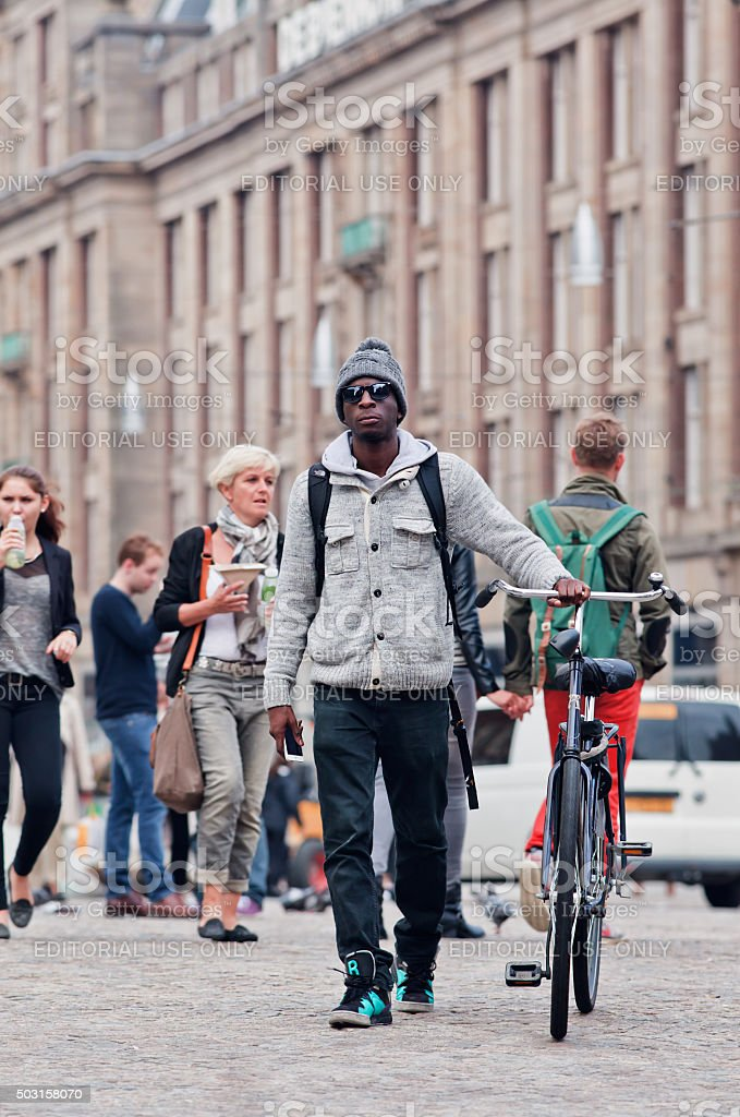 Casual dressed afro man with bicycle on Amsterdam Dam Square stock photo